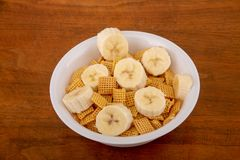 Crunchy Corn Cereal with Sliced Bananas. A Crunchy, Square, Corn Cereal with Sliced Bananas in a White Bowl on a Wood Table royalty free stock photos