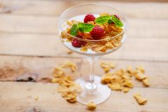 Crunchy corn flakes with raspberry in a glass cup on a wooden ta. Gold crunchy corn flakes with raspberry in a glass cup on a wooden table Stock Images