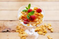 Crunchy corn flakes with raspberry in a glass cup on a wooden ta. Gold crunchy corn flakes with raspberry in a glass cup on a wooden table Royalty Free Stock Photos
