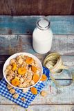 Crunchy with dried apricots. In a bowl of milk on a wooden background royalty free stock photos