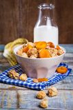 Crunchy with dried apricots. In a bowl of milk on a wooden background stock photo