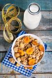 Crunchy with dried apricots. In a bowl of milk on a wooden background royalty free stock image
