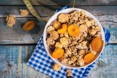 Crunchy with dried apricots. In a bowl on wooden background stock photo