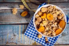 Crunchy with dried apricots. In a bowl on wooden background stock photography