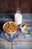 Crunchy with dried apricots. In a bowl of milk on a wooden background royalty free stock photography