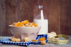 Crunchy with dried apricots. In a bowl of milk on a wooden background stock images