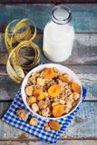 Crunchy with dried apricots. In a bowl of milk on a wooden background stock photography
