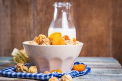 Crunchy with dried apricots. In a bowl of milk on a wooden background royalty free stock images