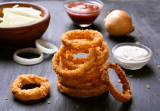 Crunchy fried onion rings. And sauce on dark background Stock Images