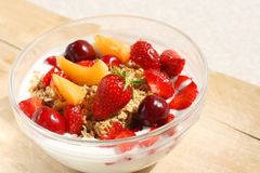 Crunchy fruit muesli (whole grain oats). Served with fresh strawberries, apricot and cherry and low fat yogurt in a glass bowl - healthy summer breakfast Royalty Free Stock Images
