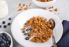 Crunchy Granola Breakfast With Fresh Blueberries. Closeup of a bowl of crunchy granola with fresh blueberries and milk stock photos