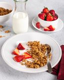 Crunchy Granola Breakfast With Fresh Strawberries. Bowl of crunchy granola with fresh strawberries and milk royalty free stock photography