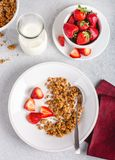 Crunchy Granola Breakfast With Fresh Strawberries. Overhead view of a bowl of crunchy granola with fresh strawberries and milk royalty free stock photos