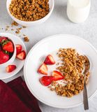 Crunchy Granola Breakfast With Fresh Strawberries. Overhead view of a bowl of crunchy granola with fresh strawberries and milk stock images