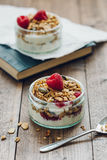 Crunchy Granola with Natural Yogurt and Fresh Raspberries on Wooden Table. A vertical food scene of breakfast pots filled with natural yogurt, homemade granola Royalty Free Stock Images