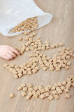 Crunchy and kid' arm. A kid' arm picking up the crunchy flakes in a shape of a smily face scattered on the wooden table royalty free stock photos