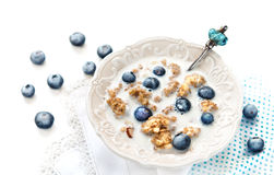 Crunchy muesli. A bowl of cereals with blueberries, nuts and with milk on a white table, healthy breakfast crunchy muesli Royalty Free Stock Photos