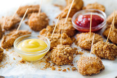 Crunchy nuggets on skewers with two sauces Royalty Free Stock Photography