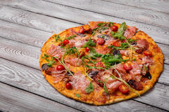 Crunchy pizza with meat and spices on a table background. Mediterranean cuisine. Nutritious snacks. Italian pizzeria. royalty free stock image