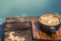 Crunchy, smażący i solący arachidy, strugający Odżywcza przekąska w małym kerimic garnku na tle naturalny brown drzewny dowcip zdjęcia royalty free