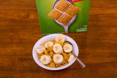 Crunchy Corn Cereal with Bananas and Box. A Crunchy, Square, Corn Cereal with Sliced Bananas in a White Bowl on a Wood Table royalty free stock photo