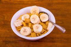 Crunchy Corn Cereal with Bananas and Milk. A Crunchy, Square, Corn Cereal with Sliced Bananas in a White Bowl on a Wood Table royalty free stock photos