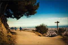 CRunning parsportsmenov på en grusväg över staden med en sikt av Barcelona, Catalonia Royaltyfri Fotografi
