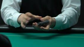 Crupié del casino que mezcla y que trata tarjetas en la tabla, juego de póker, rubor recto almacen de video