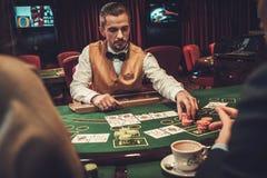 Crupié detrás de la tabla de juego en un casino foto de archivo
