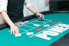 Crupié en la tabla del póker en el casino Microprocesadores y tarjetas en la tabla foto de archivo