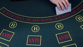 Crupié que mezcla tarjetas en una mesa de juegos del póker, cámara lenta almacen de video