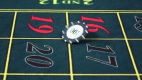 Crupié que tuerce el microprocesador en la tabla verde en el casino, cámara lenta almacen de metraje de vídeo