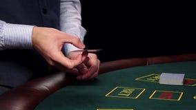 Crupié que tuerce la tarjeta y las demostraciones una en la tabla en el casino almacen de video