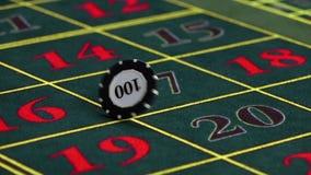 Crupié que tuerce un microprocesador en la tabla en el casino, cámara lenta almacen de video