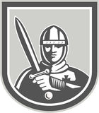 Crusader Knight With Sword Front Crest. Illustration of crusader knight in full armor brandishing a sword set inside shield crest facing front on isolated Stock Images