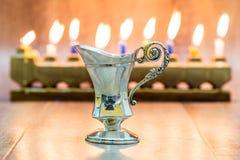 Cruse des Öls gemacht vom Silber, Chanukka mit a-Stein menorah und Kerzen Hintergrund Stockfotografie