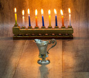 Cruse of oil  made of silver, Hanukkah. with A stone menorah and candles Royalty Free Stock Photo