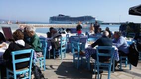 Cruse ship in port of Katakolon. Cruise ship MSC Fantasia port sea coast restaurant people seating Royalty Free Stock Photo