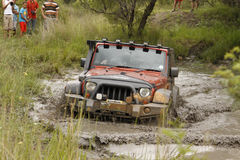 Crush Orange Jeep Rubicon crossing muddy pond Royalty Free Stock Image