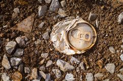 Crushed aluminium can. Detail of crushed aluminium can left on rocky soil Royalty Free Stock Images