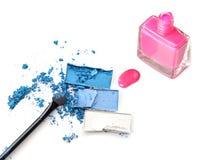 Crushed blue eye shadow with makeup brush nail polishing bottle.  stock photo