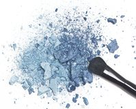 Crushed blue eyeshadow with makeup brush. On white background Royalty Free Stock Photos