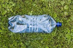 Crushed blue plastic bottle laying in grass. Pollution and environment concept royalty free stock image