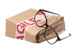 Crushed Box with Fragile Tape and Glasses. Isolated image of a crushed box with fragile tape around it and eyeglasses Royalty Free Stock Image