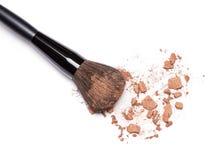 Crushed bronzing powder with makeup brush Stock Photos