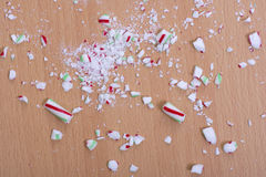 Crushed candy cane on floor. Pieces of broken Christmas candy cane shattered on wood floor Stock Photos