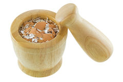 Crushed Chicken egg shells inside wooden mortar next to pestle Stock Image