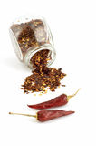 Crushed chilies. Crushed dried chilies in glass jar isolated on white background Stock Images