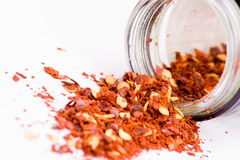 Crushed chillis. Crushed chilli spilling from glass container over white stock image