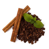 Crushed chocolate shavings pile and cinnamon sticks Royalty Free Stock Photos